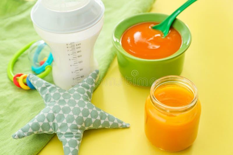 Garrafa do leite, do frasco e da bacia com comida para bebê saudável na tabela de cor imagens de stock royalty free