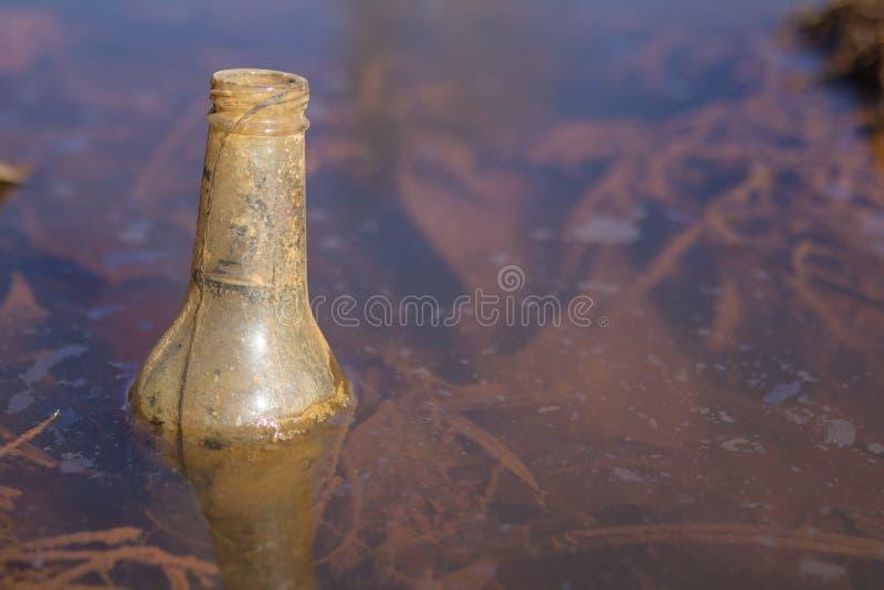 Garrafa do lixo que flutua na água fotos de stock royalty free