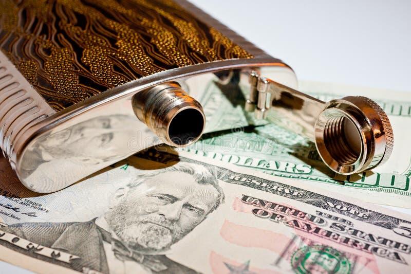 Garrafa do metal para bebidas alcoólicas e dólares do tiro do close up fotografia de stock