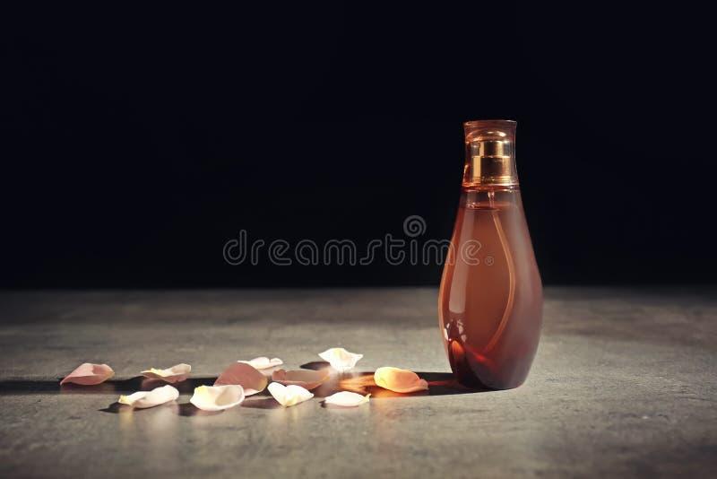 Garrafa do perfume com as pétalas da flor na tabela cinzenta fotografia de stock royalty free