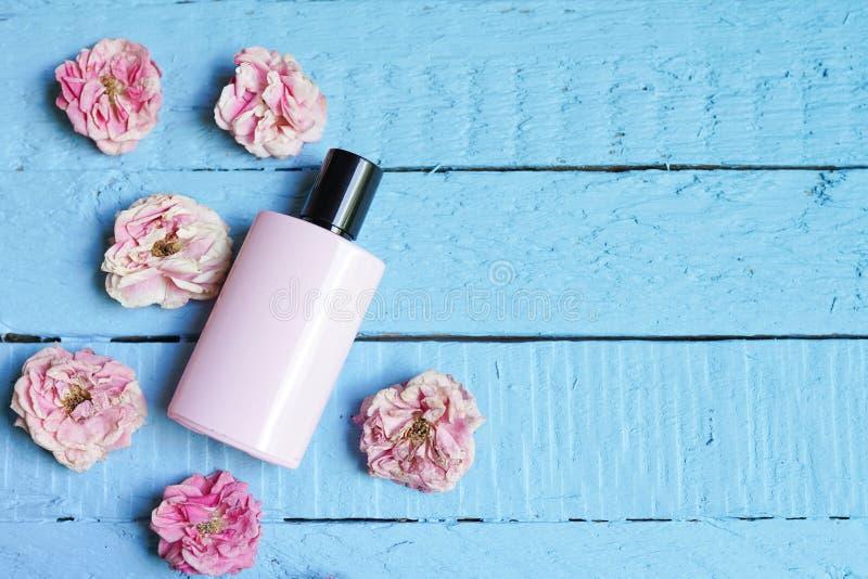 Garrafa do perfume da mulher no fundo de madeira azul com rosas Copie o espa?o fotografia de stock royalty free