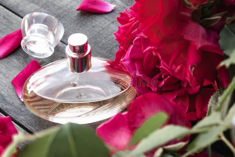 Garrafa do perfume das mulheres com as rosas vermelhas no fundo de placas de madeira escuras fotos de stock royalty free