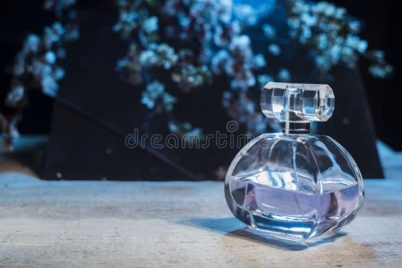 Garrafa do perfume dos woman's em um fundo de madeira em um fundo floral imagens de stock