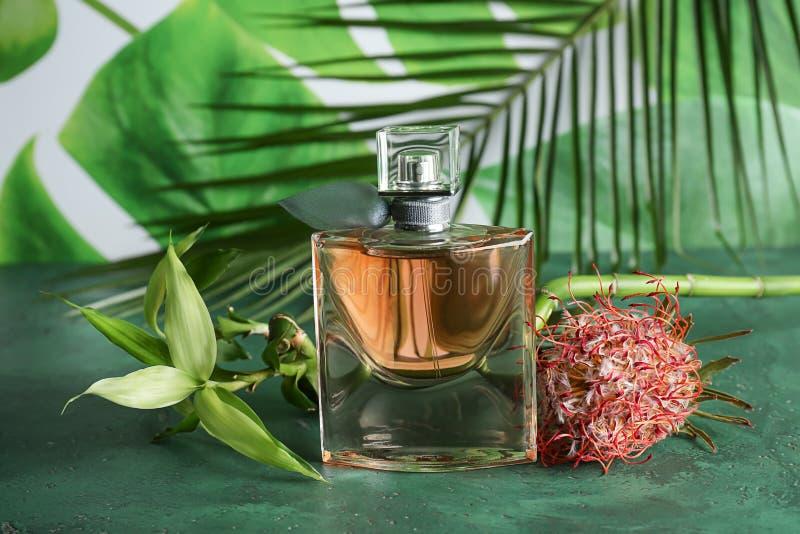 Garrafa do perfume e da flor na tabela de cor fotos de stock royalty free