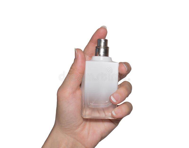 A garrafa do perfume na mão fêmea no branco isolou o fundo imagem de stock royalty free