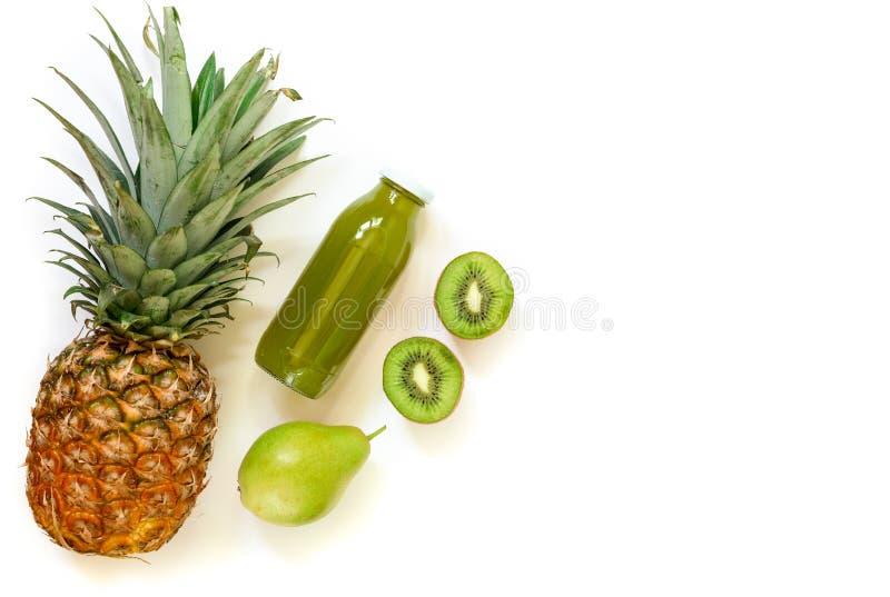 Garrafa do quivi, do abacaxi, do suco da pera isolado no branco e dos ingredientes fotografia de stock royalty free