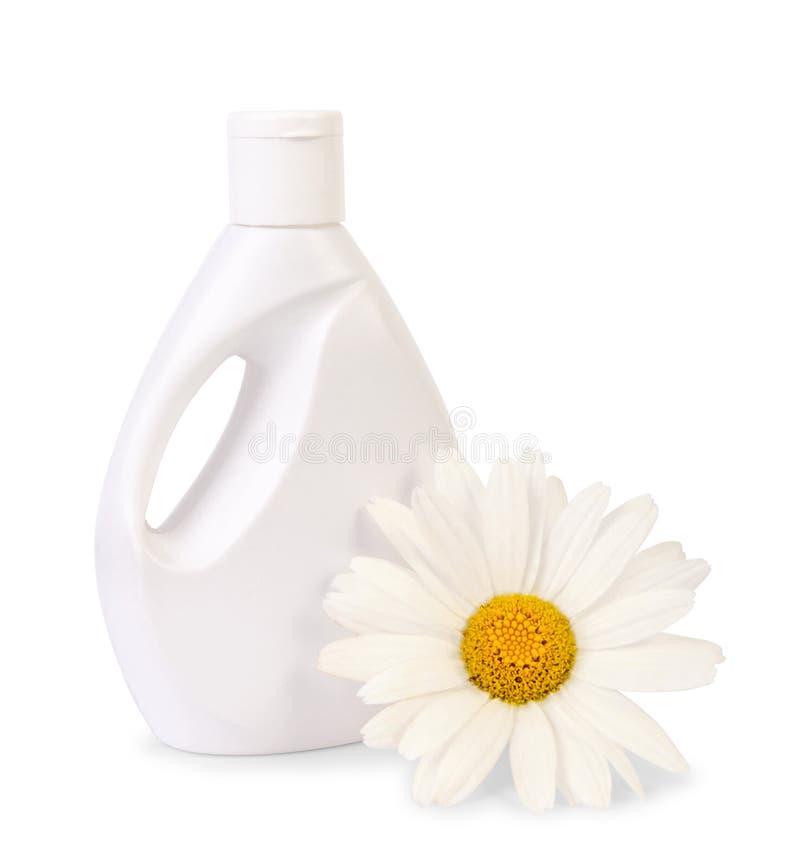 Garrafa do sabão líquido com a flor da margarida no branco imagem de stock