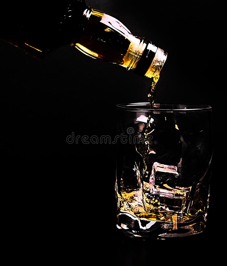 garrafa do uísque que serve um vidro que inclui cubos de gelo, fotografia de stock