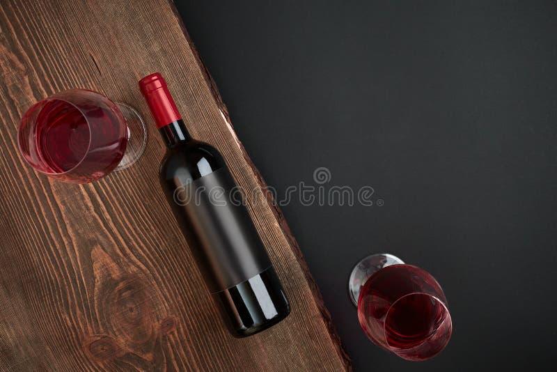 Garrafa do vinho e dos dois vidros na placa de madeira no fundo preto Vista superior com espaço da cópia fotografia de stock