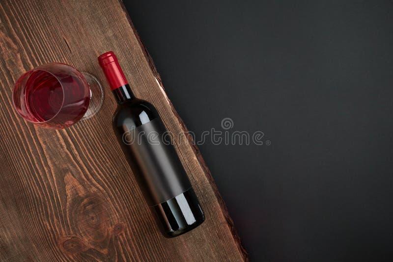 Garrafa do vinho e do um vidro na placa de madeira no fundo preto Vista superior com espaço da cópia imagens de stock royalty free