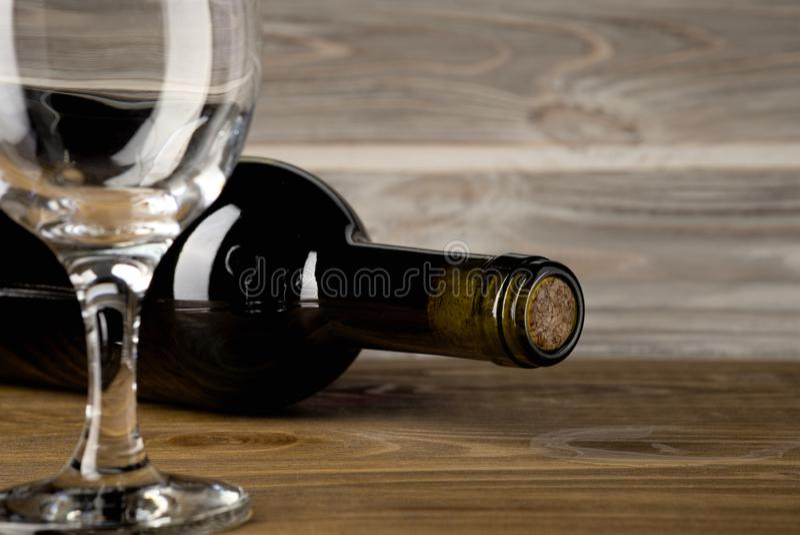 Garrafa do vinho tinto com um vidro e um corkscrew em uma tabela de madeira velha fotos de stock royalty free