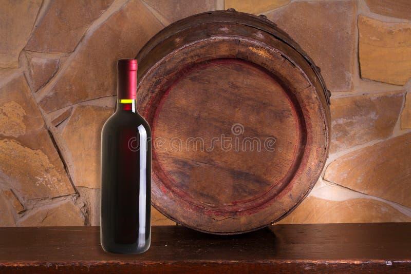 Garrafa do vinho tinto e do tambor de vinho velho na adega foto de stock