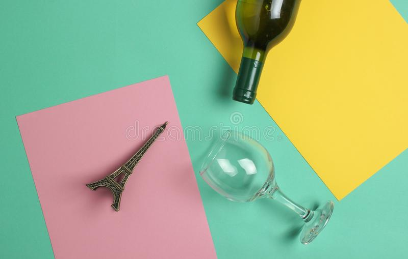Garrafa do vinho, vidro, estatueta da torre Eiffel em um fundo pastel colorido Vista superior minimalism fotografia de stock royalty free
