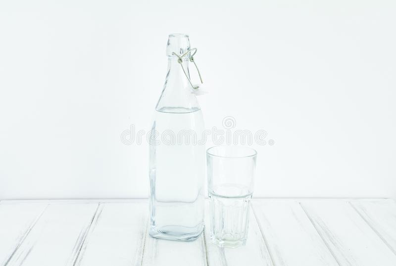 Garrafa do vintage da água e do vidro vazio na tabela branca, contra a parede branca imagens de stock royalty free