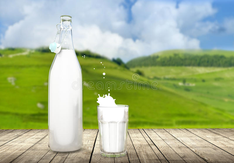 Garrafa do vintage e vidro do leite na tabela de madeira fotografia de stock