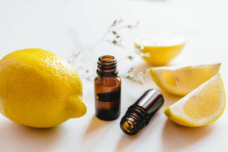 Garrafa dois do óleo essencial do limão no fundo branco imagem de stock