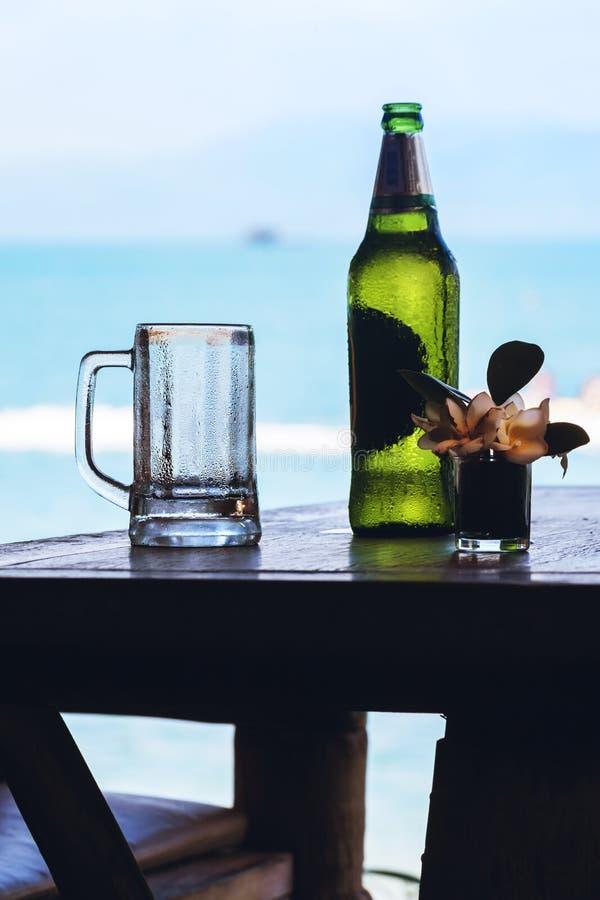 Garrafa e caneca verdes de cerveja com gotas na tabela de madeira foto de stock