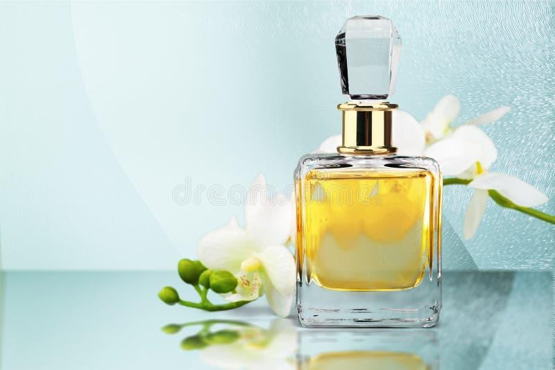 Garrafa e flores de perfume no fundo claro foto de stock