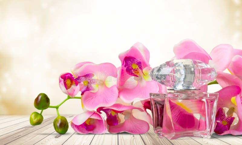 Garrafa e flores de perfume no fundo claro imagem de stock royalty free