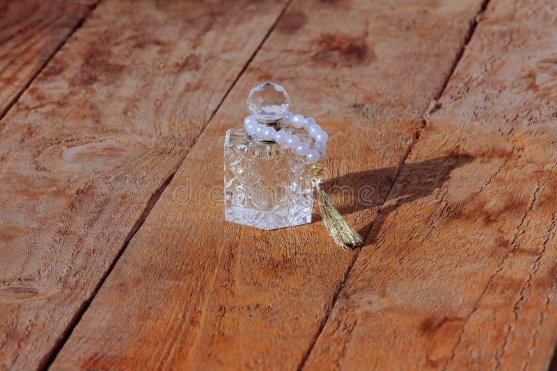 garrafa e pérolas de perfume em um fundo de madeira fotografia de stock