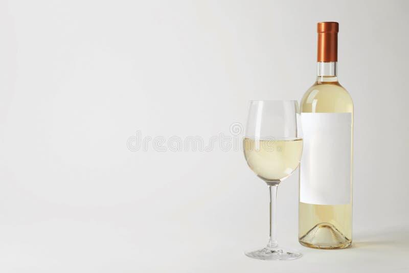 Garrafa e vidro com vinho delicioso no fundo branco imagem de stock