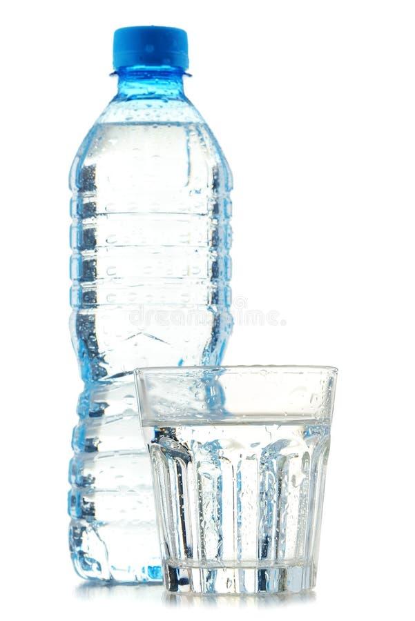 Garrafa e vidro da água mineral isolados no branco imagens de stock