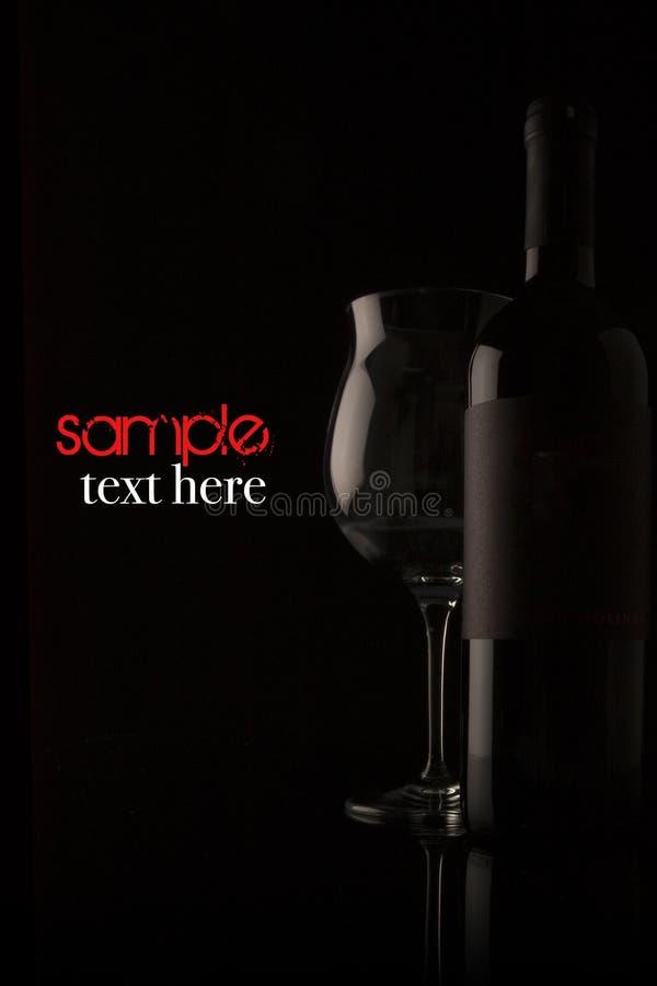 Garrafa e vidro de vinho no fundo preto imagem de stock royalty free
