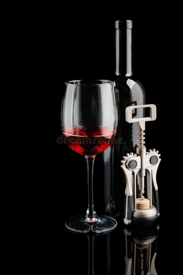 Garrafa e vidro do vinho tinto com o corkscrew no fundo escuro fotos de stock royalty free