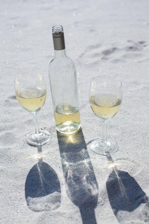 Garrafa e vidros de vinho branco na areia imagens de stock royalty free