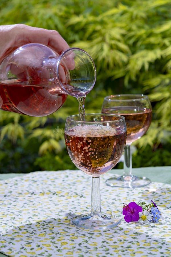 Garrafa e vidros do vinho com vinho cor-de-rosa frio e as flores selvagens no dia ensolarado do verão fotografia de stock