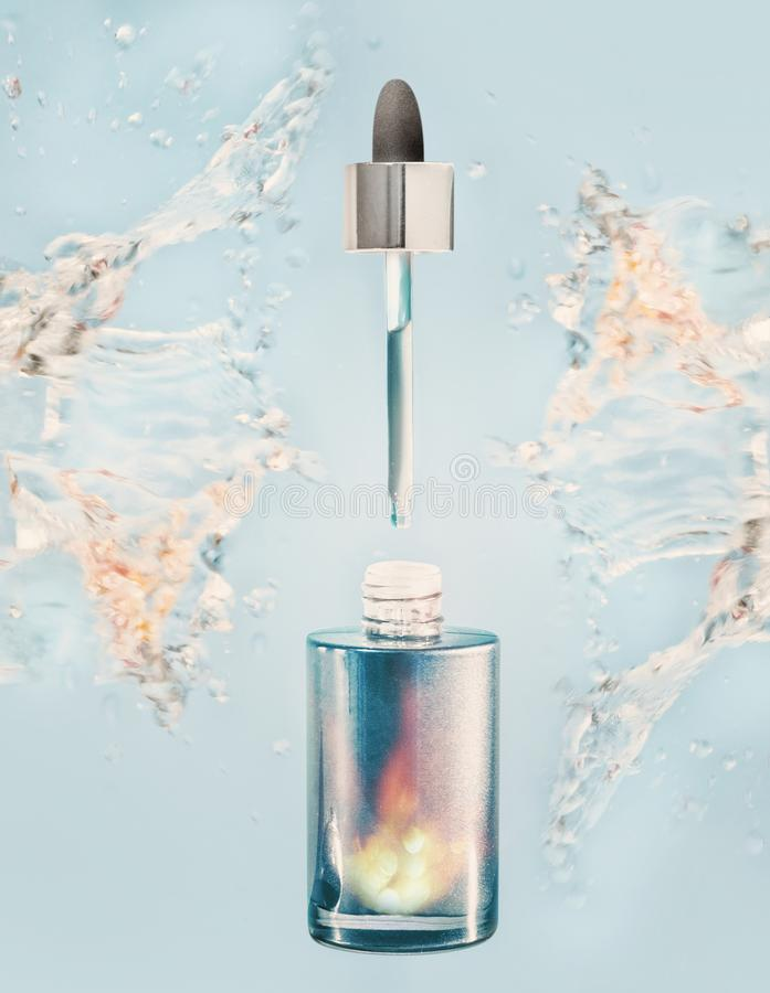 A garrafa facial de hidratação do soro ou de óleo com pipeta e água espirra no fundo azul fotos de stock