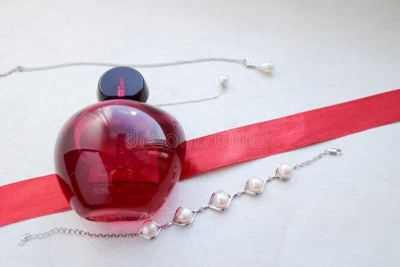 Garrafa glamoroso elegante transparente de vidro bonita vermelha dos perfumes fêmeas que encontram-se em uma fita vermelha com pé fotos de stock