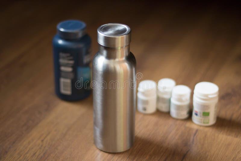 Garrafa inoxidável isolada ao lado das garrafas de comprimido fotos de stock