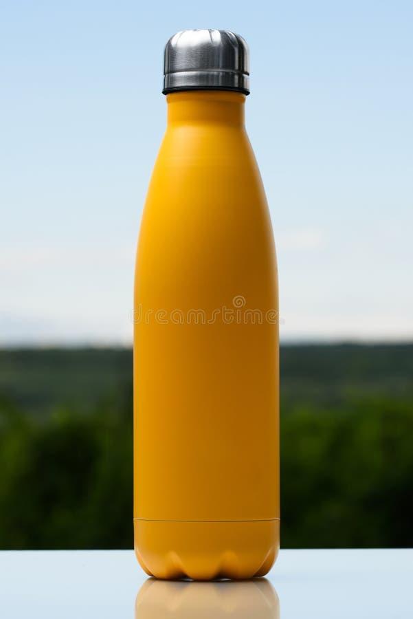 Garrafa inoxidável Thermo para a água, o chá ou o café Céu e floresta no fundo Na mesa de vidro Garrafa térmica da cor amarela ma imagens de stock