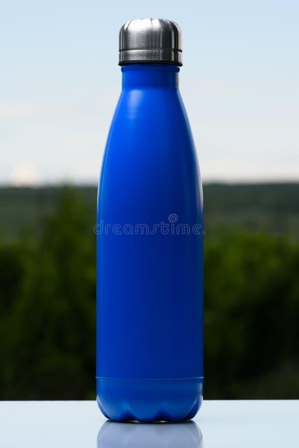 Garrafa inoxidável Thermo para a água, o chá ou o café Céu e floresta no fundo Na mesa de vidro Garrafa térmica da cor azul matte imagens de stock