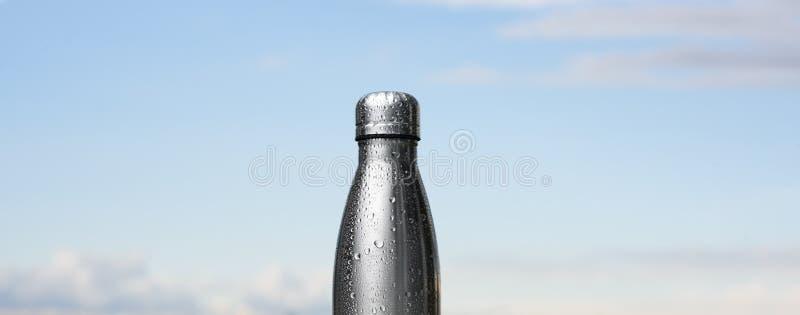 Garrafa inoxidável Thermo, pulverizada com água Céu e floresta no fundo Na mesa de vidro Garrafa térmica da cor de prata fotos de stock royalty free