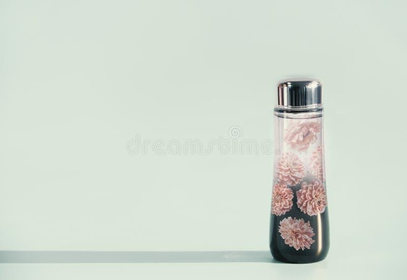 Garrafa líquida cosmética do produto com essência das flores ou tonalizador no fundo claro da hortelã, vista dianteira, espaço da foto de stock royalty free