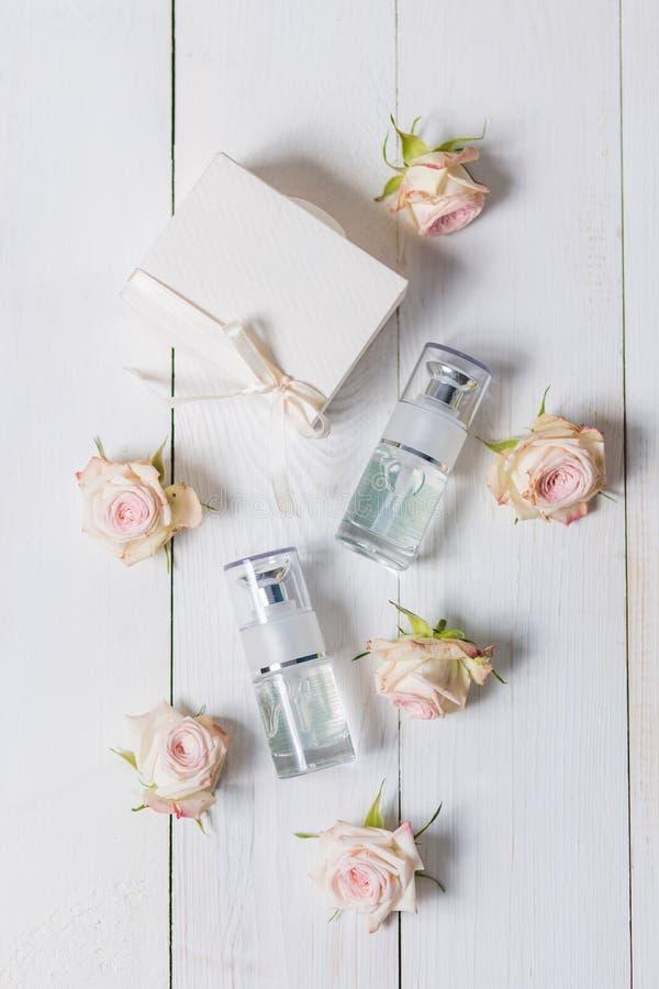 Garrafa leve do pulverizador em um fundo branco de madeira, com as rosas cor-de-rosa do pulverizador das flores imagem de stock royalty free