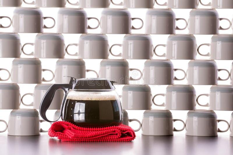 Garrafa llena del café con las tazas limpias apiladas foto de archivo libre de regalías