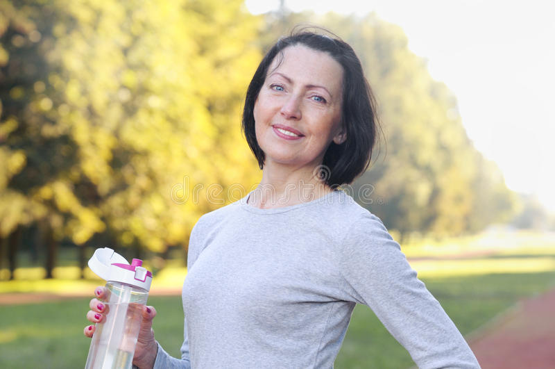 Garrafa madura desportiva da posse da mulher com água exterior no dia ensolarado no parque fotografia de stock royalty free
