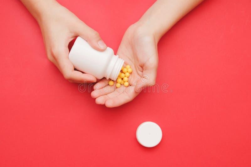 Garrafa na mão fêmea com os comprimidos amarelos no fundo vermelho, foco seletivo Conceito para a prevenção dos frios, antidepres fotos de stock