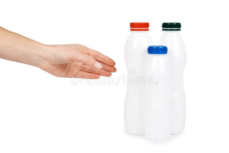 Garrafa plástica branca com iogurte da bebida ou leite com mão Isolado no fundo branco Molde da mercadoria do recipiente imagem de stock royalty free