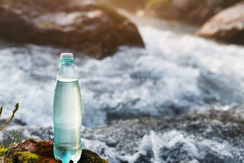 Garrafa plástica com água potável fresca no fundo de um córrego da montanha, no selvagem água fresca do ool imagem de stock