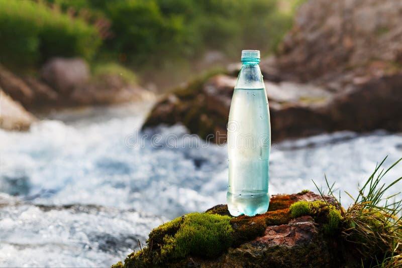 Garrafa plástica com água potável fresca no fundo de um córrego da montanha, no selvagem água fresca do ool fotos de stock