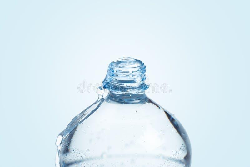 Garrafa plástica completamente com água no fundo azul fotos de stock royalty free