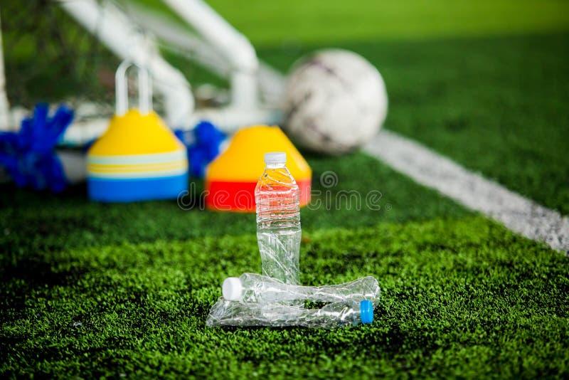 Garrafa plástica em um campo de futebol com equipamento de treino obscuro do futebol no relvado artificial foto de stock royalty free