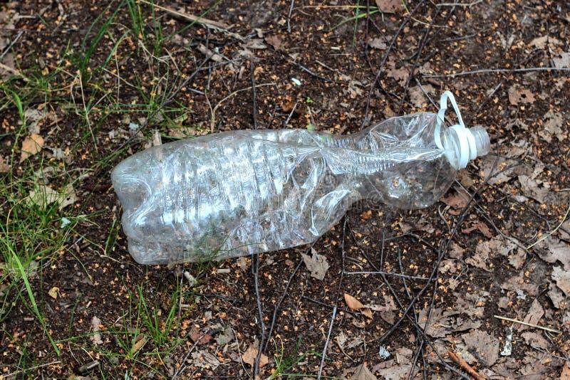 Garrafa plástica jogada afastado no lixo da floresta Problemas ecol?gicos fotografia de stock royalty free