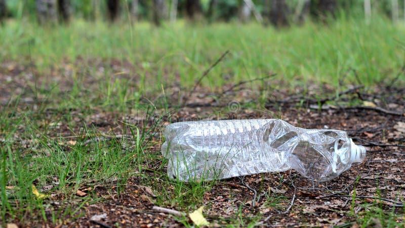 Garrafa plástica jogada afastado no lixo da floresta Problemas ecol?gicos imagens de stock royalty free