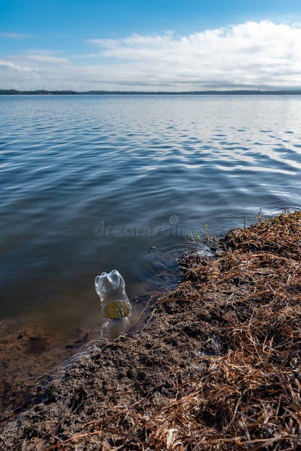 Garrafa plástica na água, na água, borda de um lago, com opinião do lago foto de stock royalty free