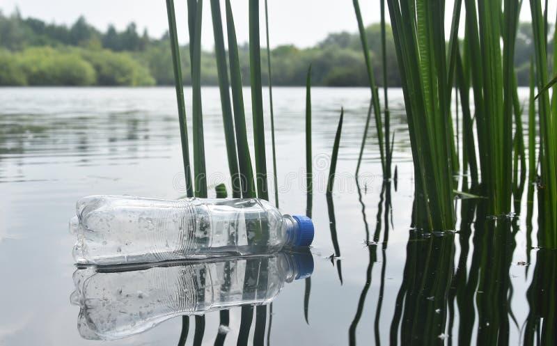 Garrafa plástica rejeitada que flutua em um lago imagens de stock